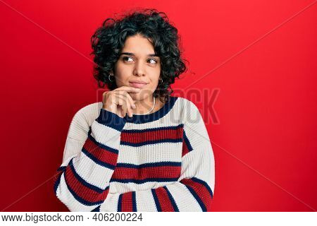 Young hispanic woman with curly hair wearing casual winter sweater thinking concentrated about doubt with finger on chin and looking up wondering