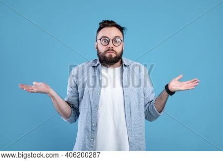 Who Knows. Confused Bearded Man In Glasses Shrugging Shoulders On Blue Studio Background. Unsure Mil