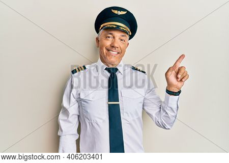 Handsome middle age mature man wearing airplane pilot uniform with a big smile on face, pointing with hand finger to the side looking at the camera.