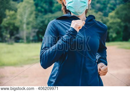 Cropped Shot Of Runner Woman Wearing Mask While Running Outdoor In Covid-19 Pandemic Outbreak. Wear