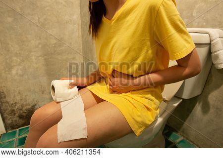 Cropped Shot Of Woman Sitting On Toilet Bowl With A Roll Of Toilet Paper In Her Hand, She Suffering
