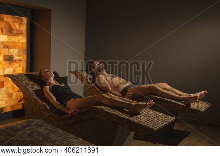 Couple In Love Relaxing In Spa Center Himalayan Salty Room, Lying On Heat Beds And Enjoying Halother
