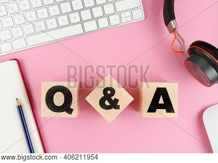 Q And A On Wooden Blocks On Pink Desk With Computer Keyboard, Headphones And Notepad