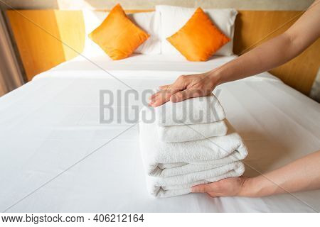 Close Up Of Hotel Maid Arranging The Stack Of Towels On Bed. Conceptual Of Female Chambermaid Making