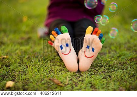 Child Feet With Painting Smiles Lying On Green Grass With Bubble