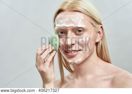 Happy Young Caucasian Man With Long Blond Hair Using Sponge For Face Washing Standing On Light Backg