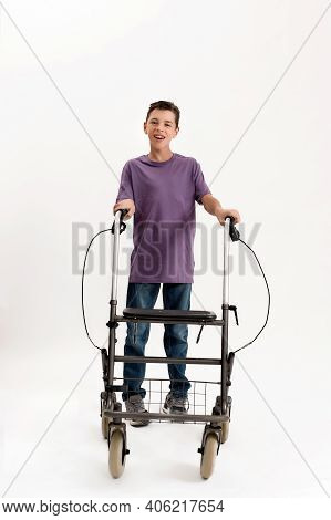 Full Length Shot Of Happy Teenaged Disabled Boy With Cerebral Palsy Looking At Camera, Taking Steps