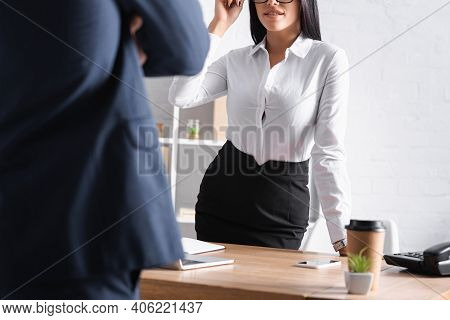 Cropped View Of Smiling, Sexy Businesswoman Seducing Colleague In Office, Blurred Foreground.