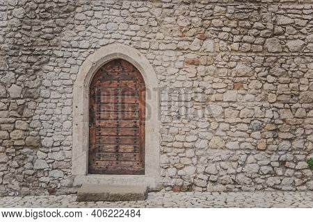 Ancient Wooden Arcade Door With Iron Rivets At Wall Of Old Building. Heavy Closed Door On A Stone Wa