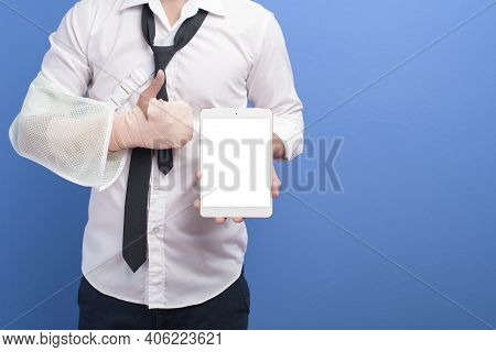 Young Businessman With An Injured Arm In A Sling Using A Tablet Over Blue Background In Studio, Insu
