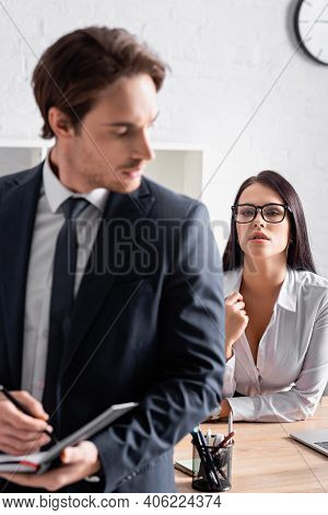 Passionate Secretary In Eyeglasses Seducing Businessman On Blurred Foreground.