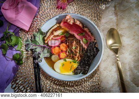 Seared Pink Ahi Tuna Ramen Garnished With Soft Boiled Egg Seaweed Strips Radish And Multicolored Sli