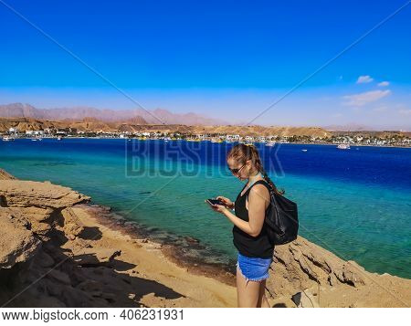 Young Caucasian Woman Tourist Looks At A Photo On A Smartphone Screen In Sharm El Sheikh (egypt). Fe