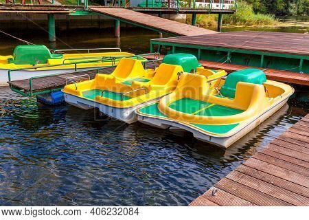Pedal Boats Or Paddle Boats Catamarans Station. Yellow Water Bicycles Locked At Lake Marina Dock Pie