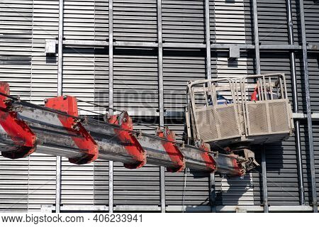 Arrow Of A Construction Truck Crane With A Cradle On The Facade Of A Building, Repair Work