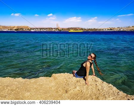 Young Pretty Caucasian Woman Sitting, Smiling, On A Rock Above The Turquoise-azure Water Of The Red