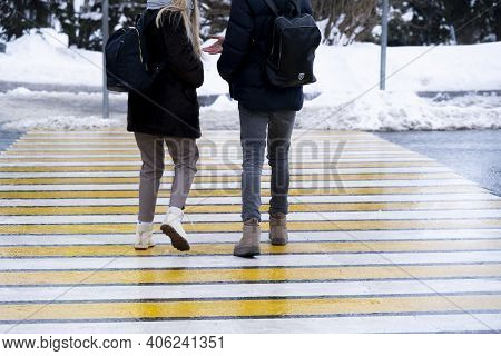 A Pair Of Pedestrians Are Crossing The Pedestrian Crossing.