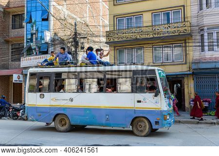 KATHMANDU, NEPAL - CIRCA NOVEMBER 2015: Men travel on top of a bus. Traveling on bus tops was authorized for a few months because of fuel shortage following a blockade at the India-Nepal border.
