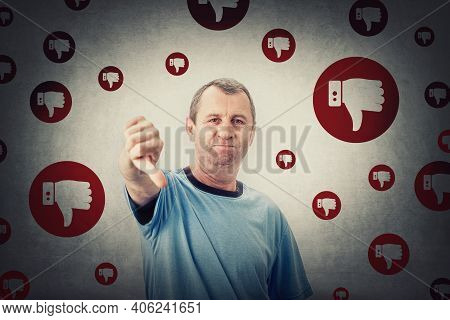 Displeased Middle Aged Man Shows Thumbs Down, Negative Gesture And Bad Feedback. Rejection And Refus