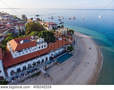 Zanzibar Aerial Shot Of Stone Town Embarkment With Traditional Dhow Fisherman Boats In The Ocean At