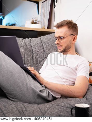 Portrait Of Male Programmer In A White T-shirt And Glasses Using Programs Computer Code In A Home. W
