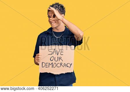 Young handsome man holding save our democracy protest banner smiling happy doing ok sign with hand on eye looking through fingers
