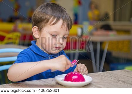 Cute Baby Boy Eat Honey Toast In The Restaurant. Little Kid Is Eating Donuts. The Child Eats In The