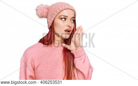Young caucasian woman wearing casual clothes and wool cap hand on mouth telling secret rumor, whispering malicious talk conversation