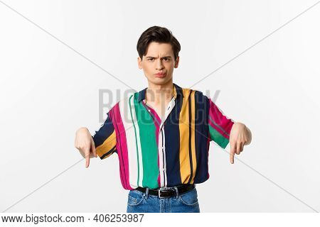 Skeptical And Displeased Queer Man Pointing Fingers Down, Grimacing And Judging Something Bad, Stand