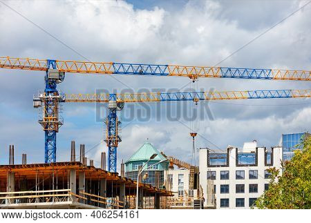 Tower Cranes With A Team Of Builders Are Erecting A New Residential Building Using A Monolithic Fram