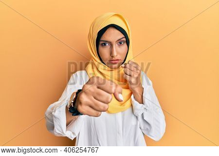 Young brunette arab woman wearing traditional islamic hijab scarf punching fist to fight, aggressive and angry attack, threat and violence