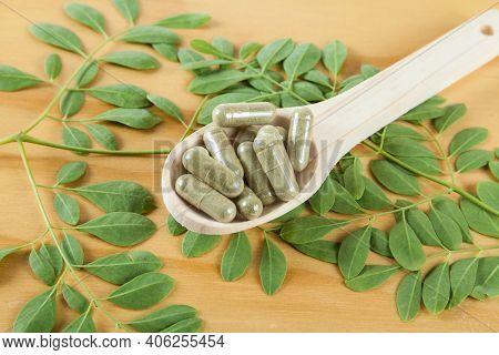 Wooden Spoon With Capsules With Powder Moringa (moringa Oleifera)