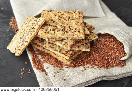 Stack Of Multigrain Crispbread With Flax Seeds On Linen Napkin Background.