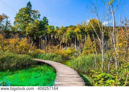 Wooden footbridge over a picturesque shallow lake. Plitvice Lakes are beautiful karst lakes of turquoise color. Plitvice Lakes Park in Croatia. Travel to Central Europe