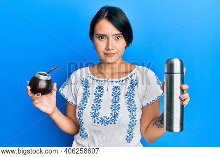Beautiful young woman with short hair drinking mate infusion skeptic and nervous, frowning upset because of problem. negative person.