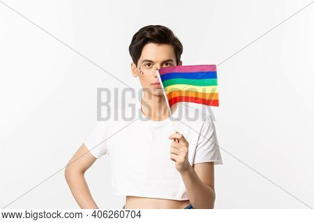 Lgbtq Community. Attractive Queer Man With Flitter On Face, Waving Pride Rainbow Flag And Looking At