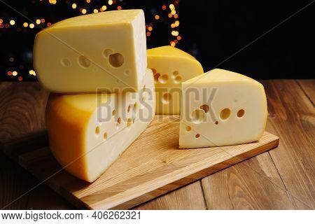 Cheese On Table On The Dark Background. Medium Hard Cheese Head Edam, Gouda, Parmesan On Wooden Boar