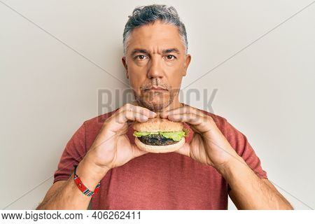 Handsome middle age mature man eating a tasty classic burger relaxed with serious expression on face. simple and natural looking at the camera.