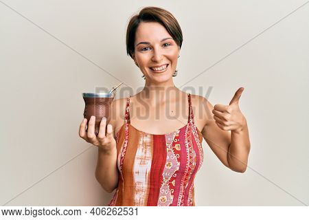 Young brunette woman with short hair drinking mate infusion smiling happy and positive, thumb up doing excellent and approval sign