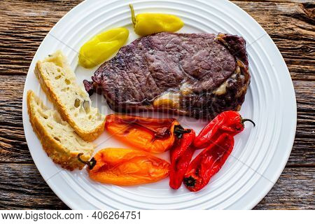 Club steak with grilled sweet peppers on white plate top view