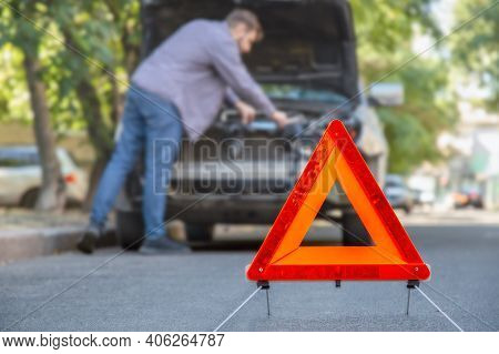 Man Fixing Car On Road. Car Breakdown While Driving. Driver Looks On Breakdown Under The Hood Of Car