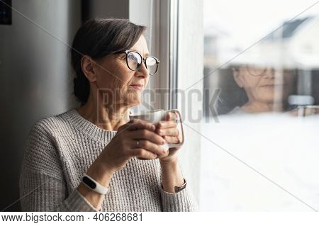 Close-up Portrait Of Senior Older Woman Wearing Glasses Enjoys Morning Coffee In The Kitchen At Home