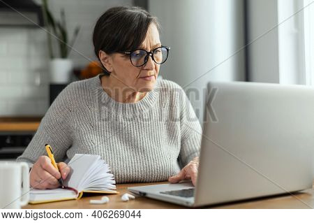 Concentrated Retirement Woman Using A Laptop Sitting At The Desk In The Kitchen For Remote Work, Stu