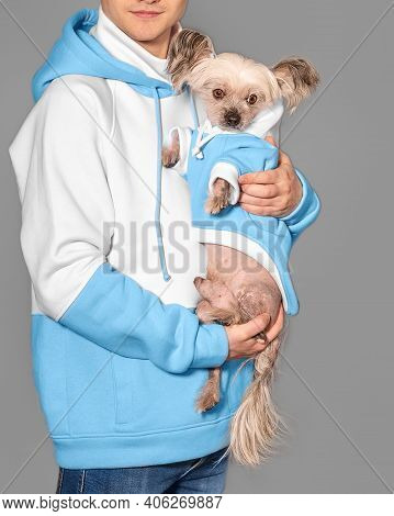 A Young Guy Holds A Chinese Crested Dog In His Arms. Both Wear The Same Clothes