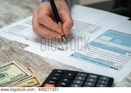 Man Filling Us Tax Form. Tax Form Us Business Income Office Hand Fill Concept. Tax Return Form 1040
