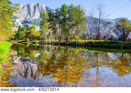 The rock-monolith El Capitan is reflected in the smooth water. Charming little lake in the Yosemite Valley. Yosemite Park is located on the slopes of the Sierra Nevada