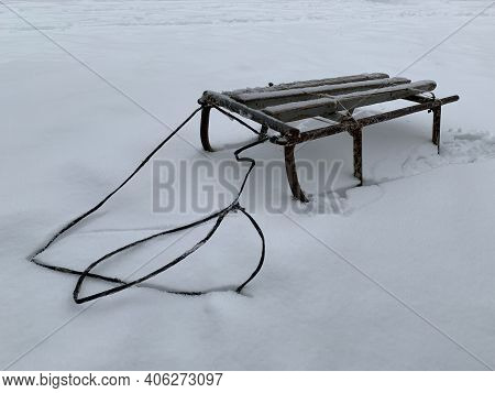 Old Metal Sleigh In The Snow. A Product For Winter Skiing. Children's Sled With Rope, On A White Bac