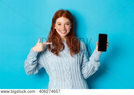 Satisfied Redhead Girl Pointing At Phone Screen, Showing Smartphone App Or Online Promo And Smiling,