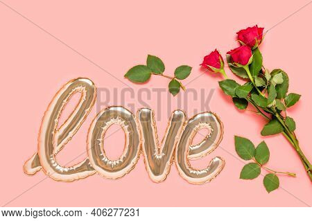 Golden Foil Balloon In Shape Of Love Word And Three Red Roses Bouquet On Pink Background. Love And D