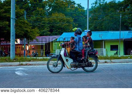 A Man With Three Children Rides A Motorbike. Motorbike In Asia. Langkawi, Malaysia - 07.18.2020